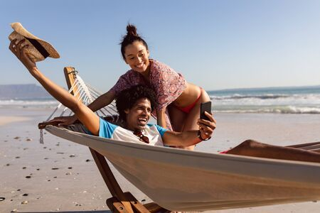 Front view of happy young Mixed-race couple taking selfie with mobile phone on the beach