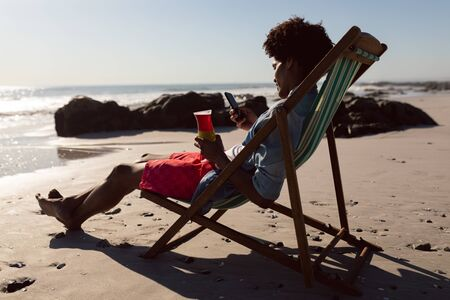 Side view of young African-american man using mobile phone while having cocktail in a beach chair Stok Fotoğraf