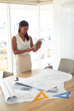Side view of beautiful mixed race female architecture using digital tablet at table in a modern office