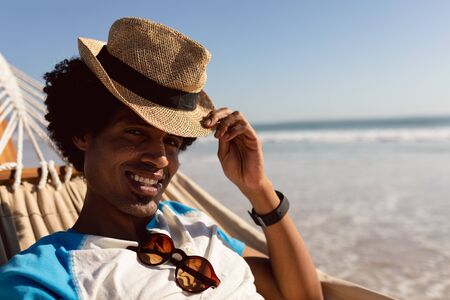 Portrait of young African-american man with hat relaxing in a hammock on the beach Stok Fotoğraf
