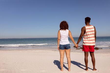 Rear view of Mixed-race couple holding hands and standing on beach in the sunshine Stock Photo