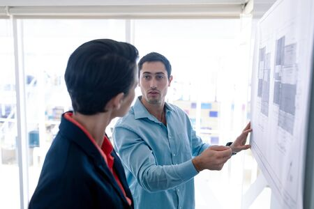 Side view of diverse architects discussing over blueprint on glass board in a modern office