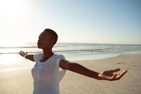 Front view of young African-american woman performing yoga on the beach Stok Fotoğraf