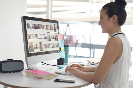 Side view of Asian female graphic designer working on computer at desk in a modern office Stock Photo