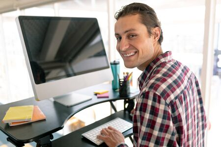 Portrait of Caucasian male graphic designer working on computer at desk in office