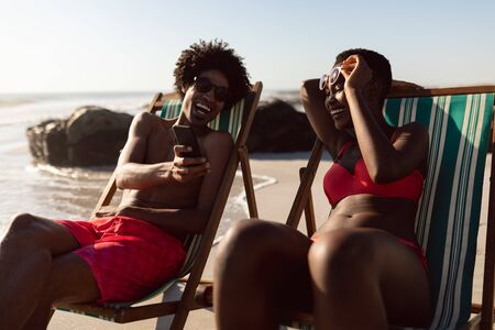 Front view of happy African-american couple having fun on mobile phone while relaxing in a beach chair on the beach