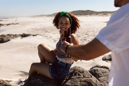 Rear view of happy young Mixed-race couple toasting beer bottle on beach in the sunshine Stok Fotoğraf