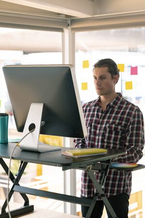 Side view of Caucasian male graphic designer working on computer at desk in office Stock Photo