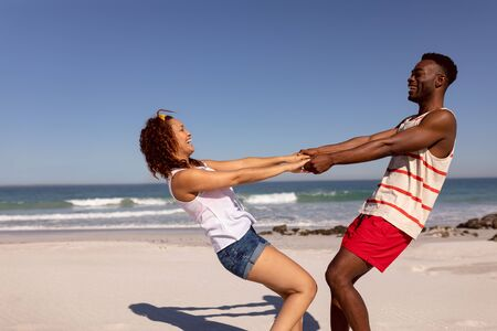 Front view of happy Mixed-race couple having fun on beach in the sunshine