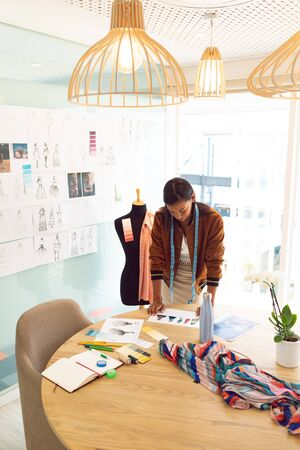 High angle view of mixed race female fashion designer looking at sketches on table in a modern office Stock Photo - 124672964