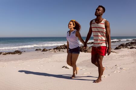 Front view of Mixed-race couple holding hands and walking on beach in the sunshine