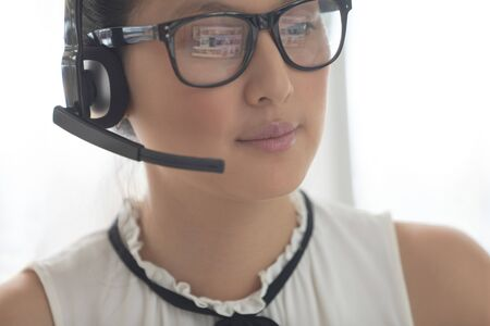 Front view of beautiful Asian female customer service executive with headset looking away in a modern office