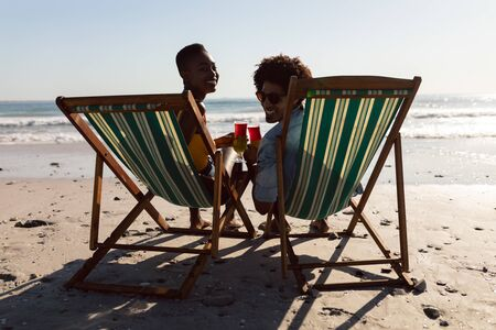 Rear view of happy African-american couple holding cocktail glasses while relaxing in a beach chair on the beach