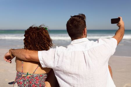 Rear view of Mixed-race couple taking selfie with mobile phone on beach in the sunshine 版權商用圖片