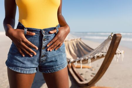 Mid section of African-american woman standing with her thumbs in belt loops on the beach