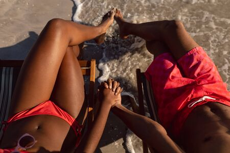 Low section of African-american couple relaxing with hand in hand on the beach