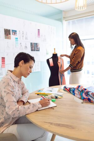 Side view of attentive mixed race female fashion designers working in a modern office. Mixed race girls working in the background