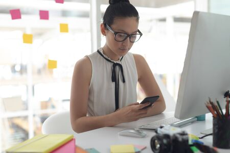 Front view of beautiful Asian female graphic designer using mobile phone at desk in a modern office