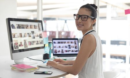 Side view of Asian female graphic designer looking at camera while working on computer at desk in a modern office
