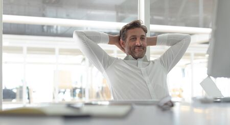 Front view of happy Caucasian business male executive with hands behind hand sitting at desk in a modern office
