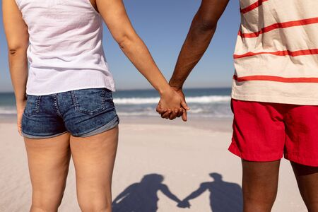 Mid section of Mixed-race couple holding hands and standing on beach in the sunshine