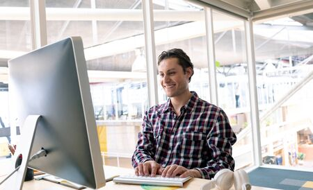 Side view of happy Caucasian male graphic designer working on computer at desk in a modern office