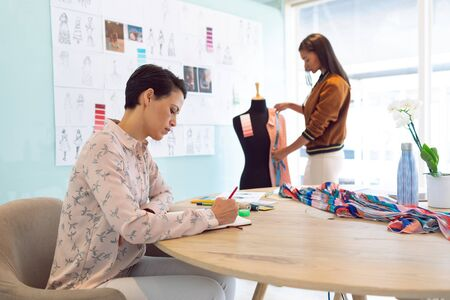 Side view of attentive mixed race female fashion designers working in a modern office. Mixed race female working in the background. Stock Photo