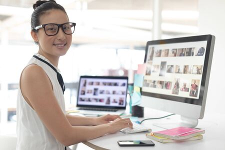Front view of Asian female graphic designer looking at camera while working on computer at desk in a modern office
