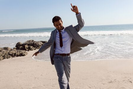 Front view of happy young Mixed-race Businessman dancing on the beach