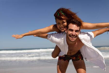 Front view of happy Mixed-race man giving piggyback to woman on beach in the sunshine Reklamní fotografie