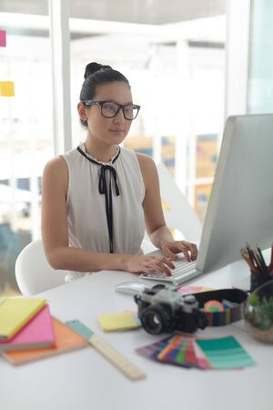 Front view of Asian female graphic designer working on computer at desk in a modern office
