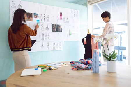 Rear view of beautiful diverse female fashion designers working in a modern office Stock Photo - 124672792