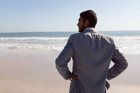 Rear view of young Mixed-race Businessman standing with hands on hips at beach Banco de Imagens