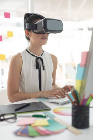 Side view of Asian female graphic designer using virtual reality headset while working on computer at desk in a modern office Stock Photo - 124672812