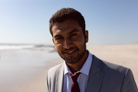 Portrait of young Mixed-race Businessman standing on the beach