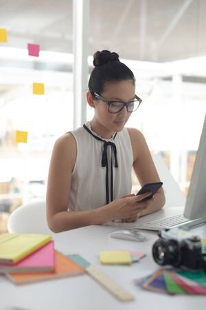 Front view of beautiful and concentrated Asian female graphic designer using mobile phone at desk in a modern office