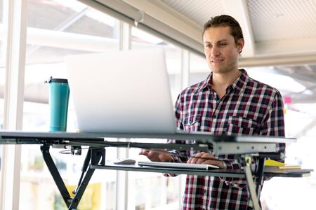Front view of Caucasian male graphic designer working on laptop at desk in office Stock Photo