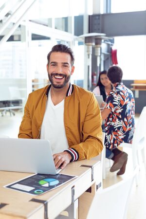 Portrait of smiling Caucasian Businessman using laptop on desk in the office while colleagues speaking together behind him