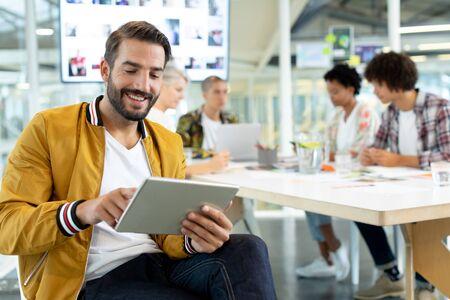 다양한 비즈니스 사람들이 사무실 회의실에서 토론하는 동안 디지털 태블릿을 사용하는 백인 남성 패션 디자이너의 전면