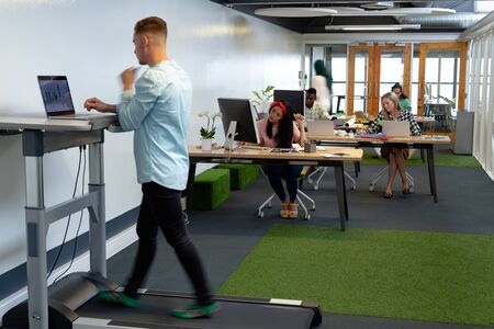 Side view of Caucasian businessman working on laptop while exercising on treadmill in a modern office Stock Photo