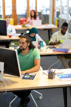 Front view of Mixed-race attentive businessman working on computer at desk in a modern office