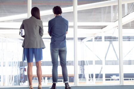 Rear view of diverse male and female architects looking through window in office Banco de Imagens