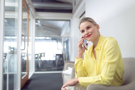 Front view of beautiful Caucasian female executive talking on mobile phone in office