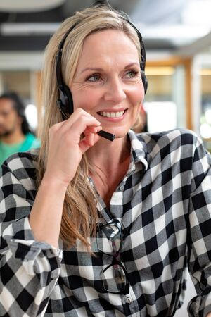 Portrait of happy Caucasian female customer service executive looking away while talking on headset in a modern office