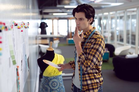 Side view of Caucasian male fashion designer looking at sketch in office Stock Photo - 124672643
