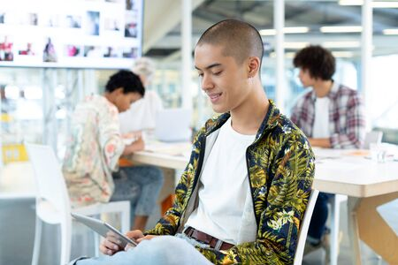 Side view of mixed race male fashion designer using digital tablet in the conference room while diverse business people discussing at office