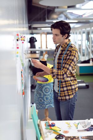 Side view of Caucasian male fashion designer looking at sketch in office Stock Photo - 124672570
