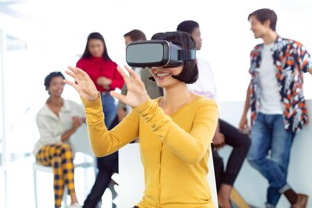 Front view of happy young Caucasian businesswoman using virtual reality headset in a modern office