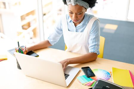 High angle view of African american female graphic designer using graphic tablet and laptop at desk in office Stock Photo - 124672574