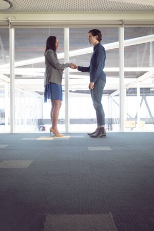 Side view of diverse male and female architects shaking hands with each other in office